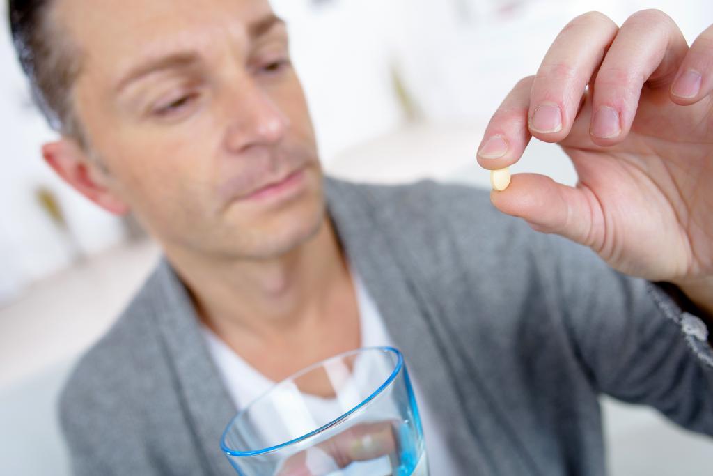 Таблетку запивают водой