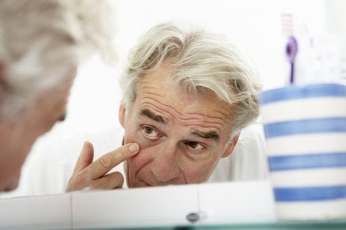 мужчина рассматривает себя в зеркало