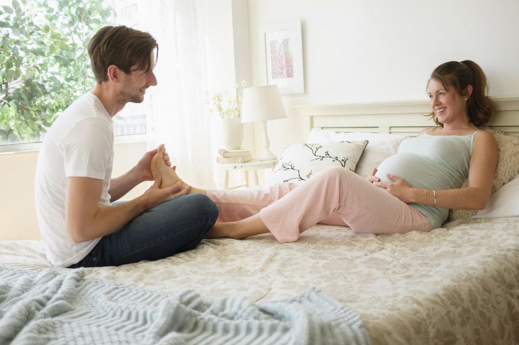 мужчина делает массаж ноги беременной женщине