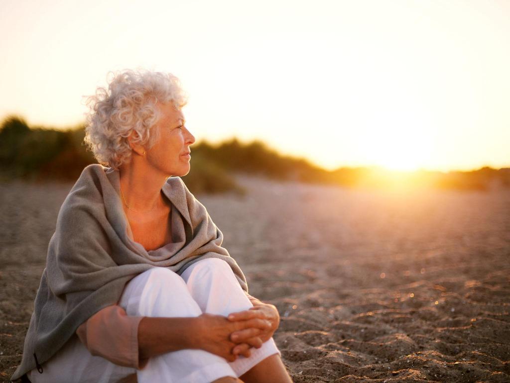 пожилая женщина сидит на песке