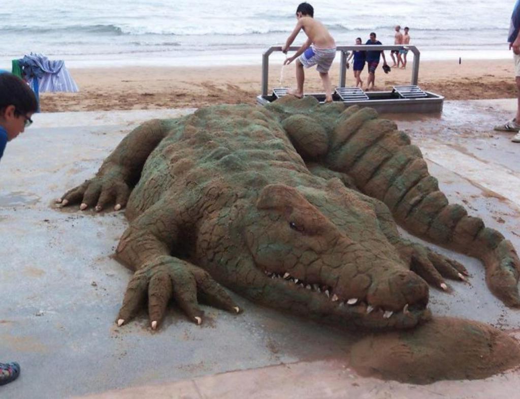 Только приглядевшись, можно заметить разницу: мужчина создает реалистичные скульптуры из песка
