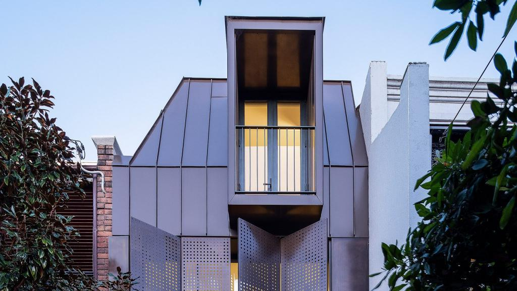 Дизайнеры решили добавить бронзовые ставни к фасаду пристройки: получилось стильно и оригинально