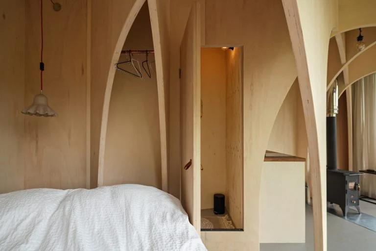 Архитекторы заполнили и без того небольшую хижину деревянными арками: выглядит так, будто внутрь поместили часовню