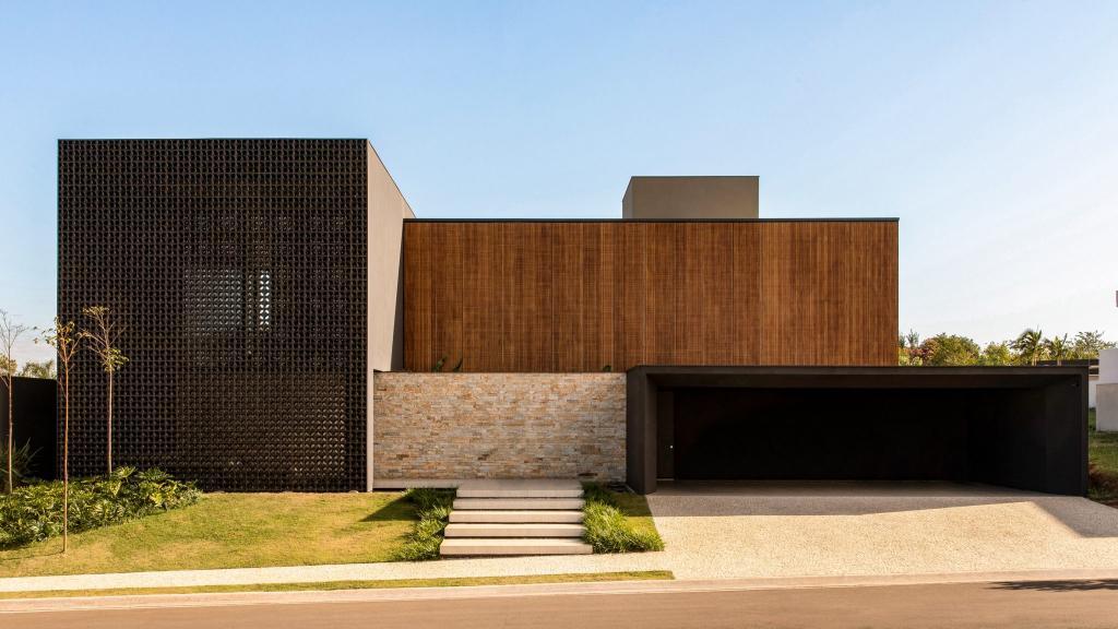Перфорированные блоки, черные кирпичи, древесина и камень покрывают дом, состоящий из трех частей: фото