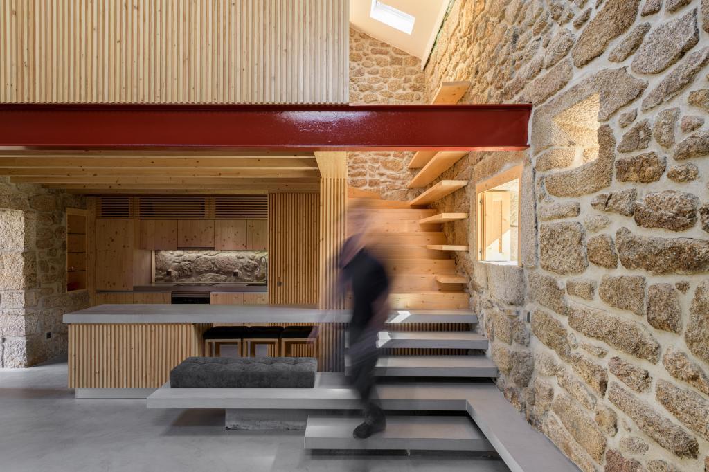 Старую пекарню превратили в семейный дом для отпуска. Внутри выделяется лестница со ступенями, которые одновременно служат столом, скамейкой и камином