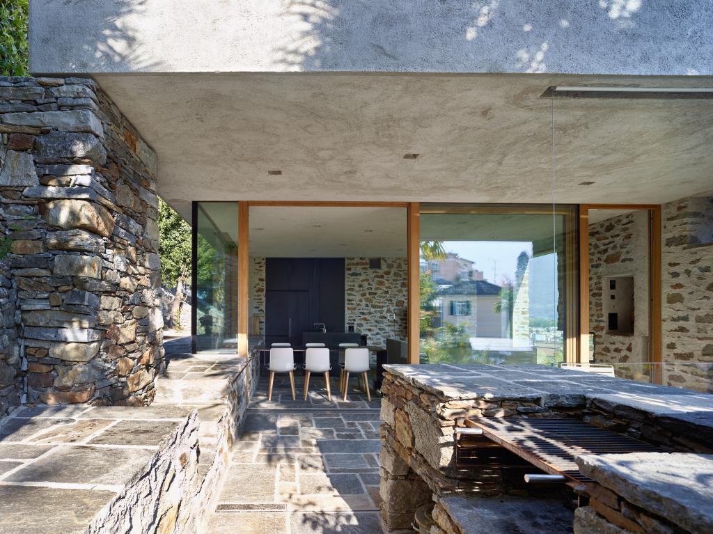 С помощью натурального камня и традиционной для Швейцарии штукатурки дизайнеры умело интегрировали дом в окрестности
