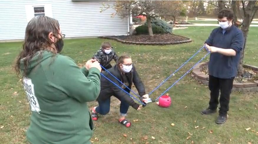 Координация и безопасность: женщина из Огайо использует большую рогатку, чтобы раздавать лакомства детям