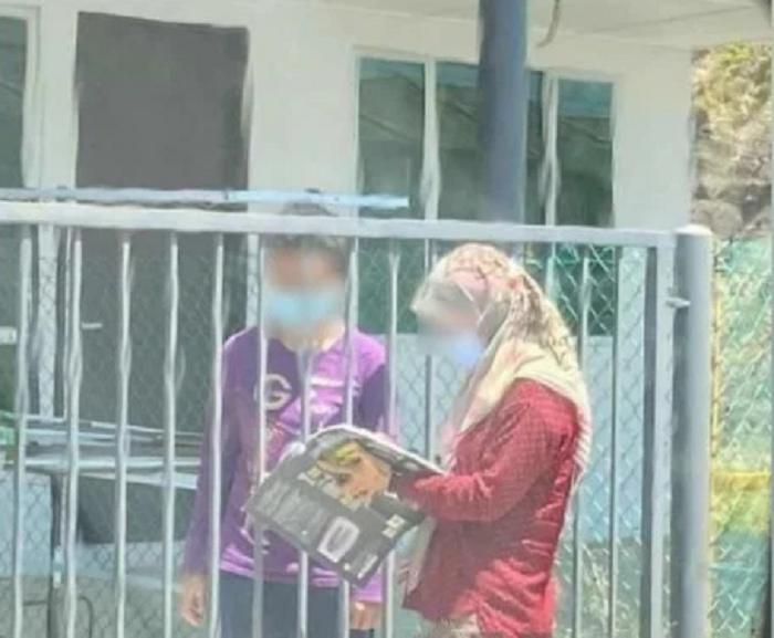 Учительница из Малайзии каждый день посещает своих учеников, чтобы поставить оценки за домашнюю работу: тетради она проверяет прямо на улице