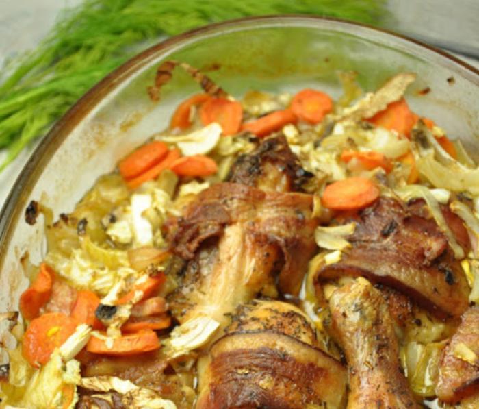 Чтобы куриные голени были сочнее, накрываю их ломтиком бекона. Тушу в духовке с пекинской капустой