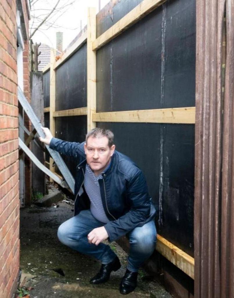 Дверь гаража открыть невозможно. За ночь возле дома мужчины вырос огромный забор