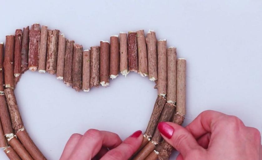 Комнату девочки можно украсить интересным венком в форме сердца: для создания понадобится картон, ветки и немного времени