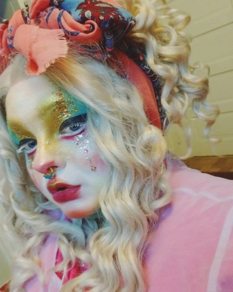 Полная модель использует макияж, чтобы превратить себя в живую куклу