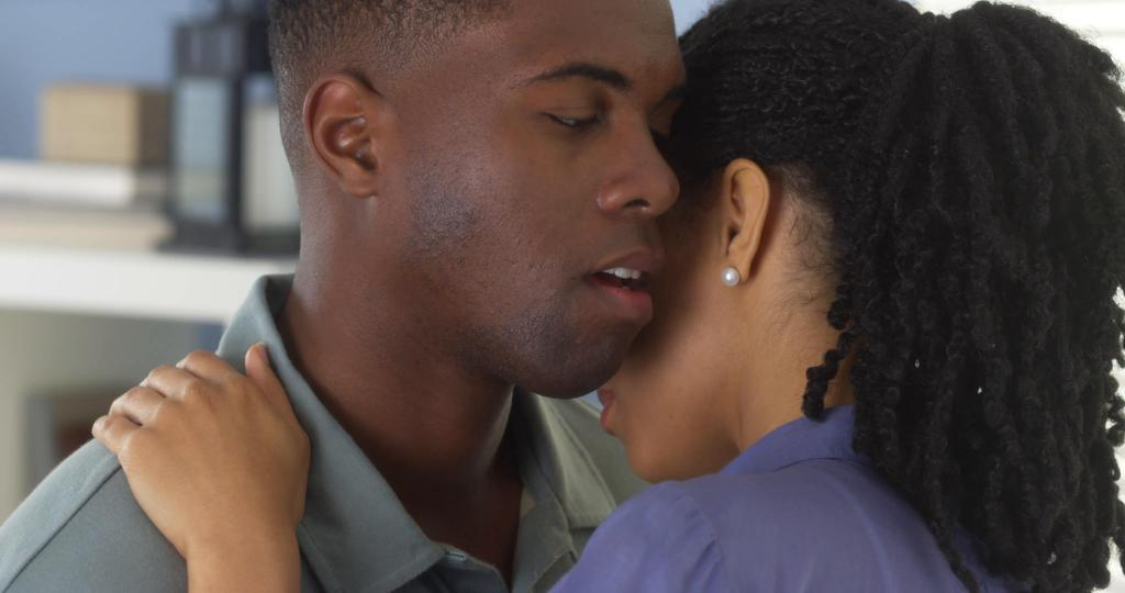A girl holds a guy by the shoulder and whispers in his ear