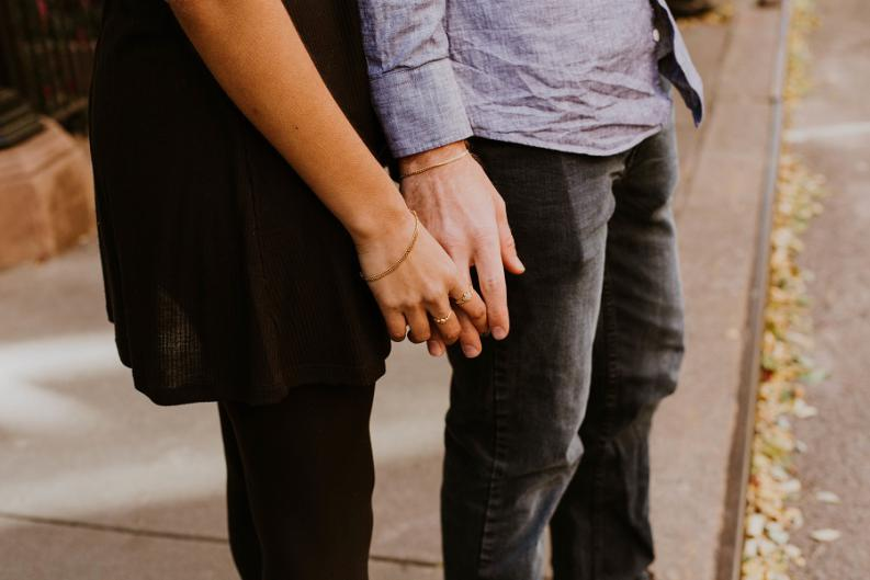 Girl and guy standing touch each other with their fingers