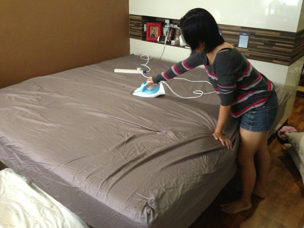 женщина гладит белье на кровати