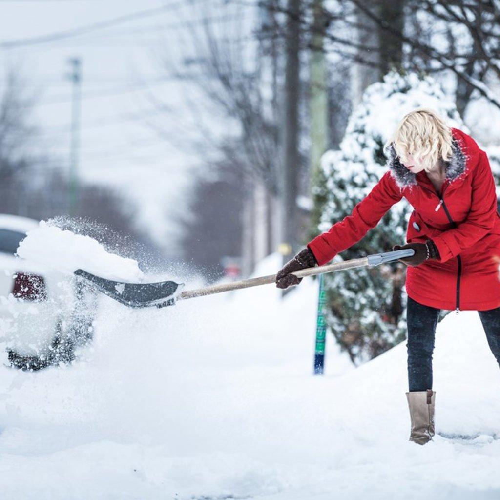 Девушка чистит снег