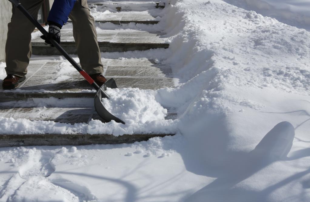 Человек чистит снег на ступеньках