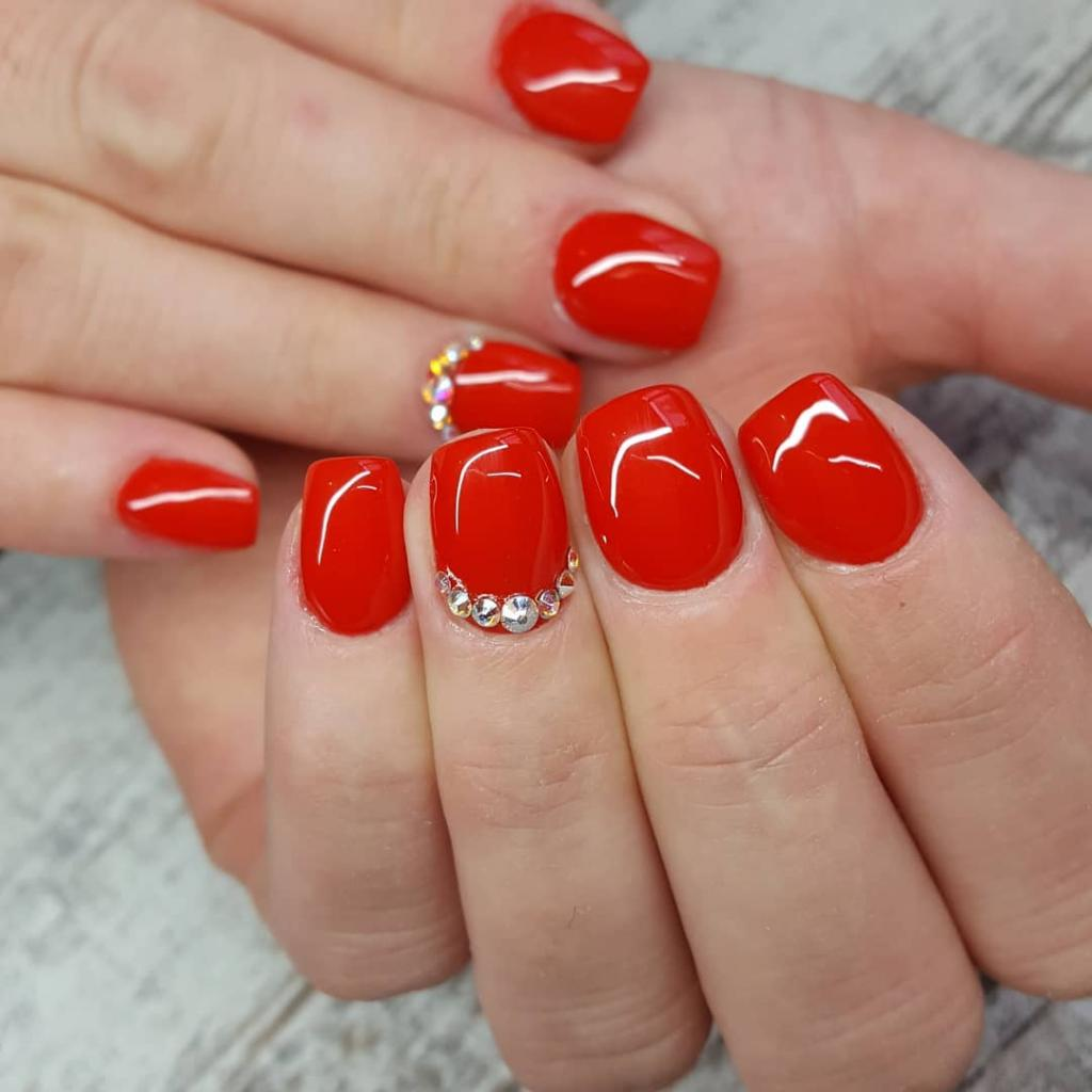 rhinestones next to the cuticle on red nails