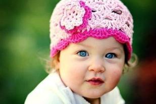 Детская шапка-косынка связана спицами из хлопковой пряжи узором с листьями. Завязочки и внешний край шапочки выполнены крючком. Так же крючком связан декор