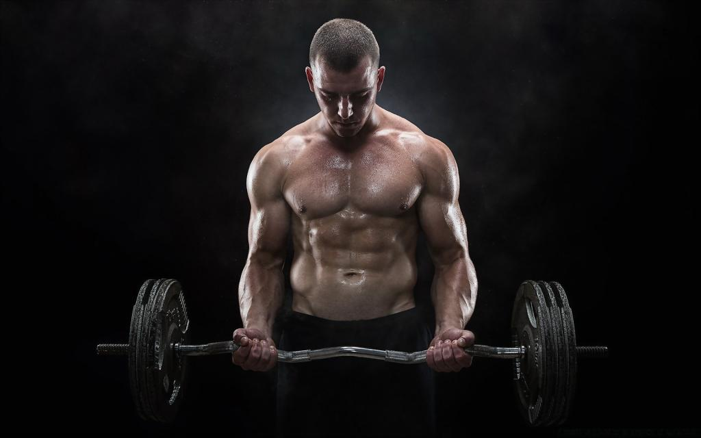 A man shakes his biceps with a barbell.