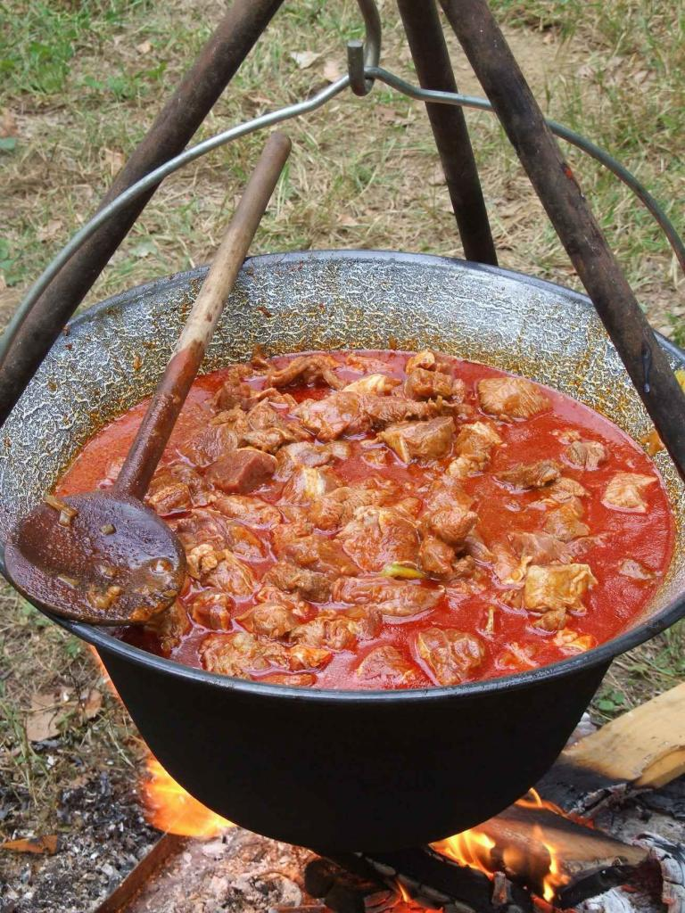 Cook the goulash in a pot at the stake.