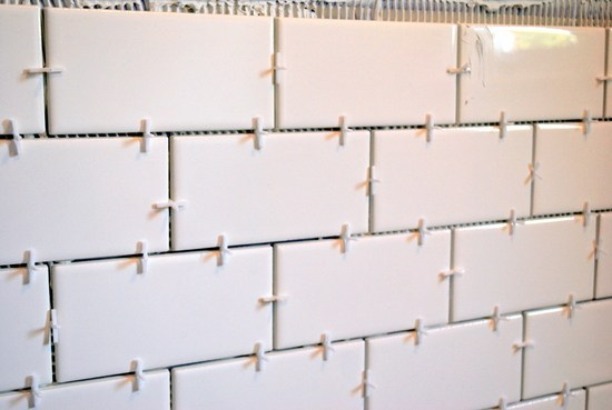 start laying tiles in the bathroom on the walls