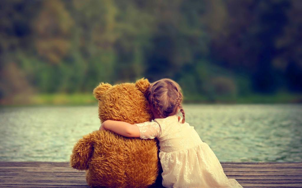 Ребенок обнимается с медведем