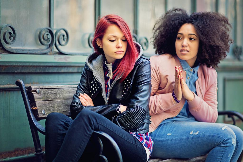 Two girlfriends are sitting on a bench