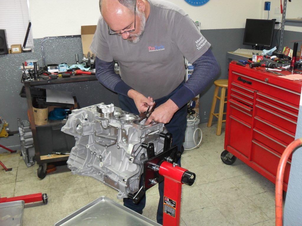 Автомеханик ремонтирует двигатель