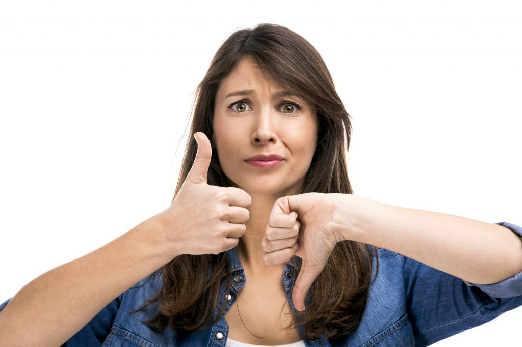 woman holds thumbs up and down