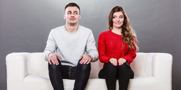 man and woman are sitting on the couch