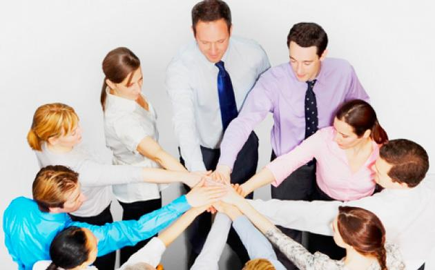 employees stand in a circle with outstretched arms