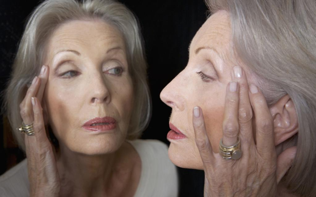 old woman looks at herself in the mirror