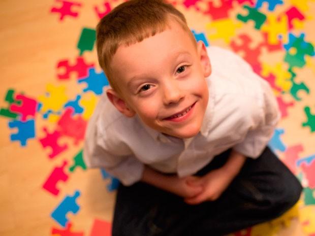 мальчик олигофрен на ковре с пазлом