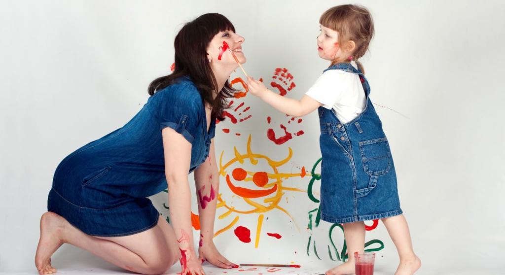 girl draws on mom's cheek
