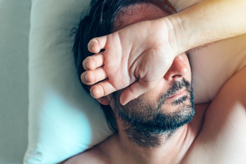 мужчина спит, положив руку на лицо
