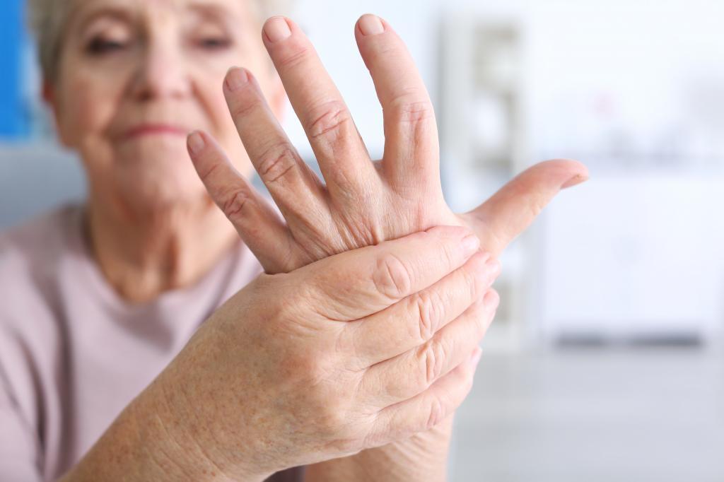 пожилая женщина держит свою левую руку