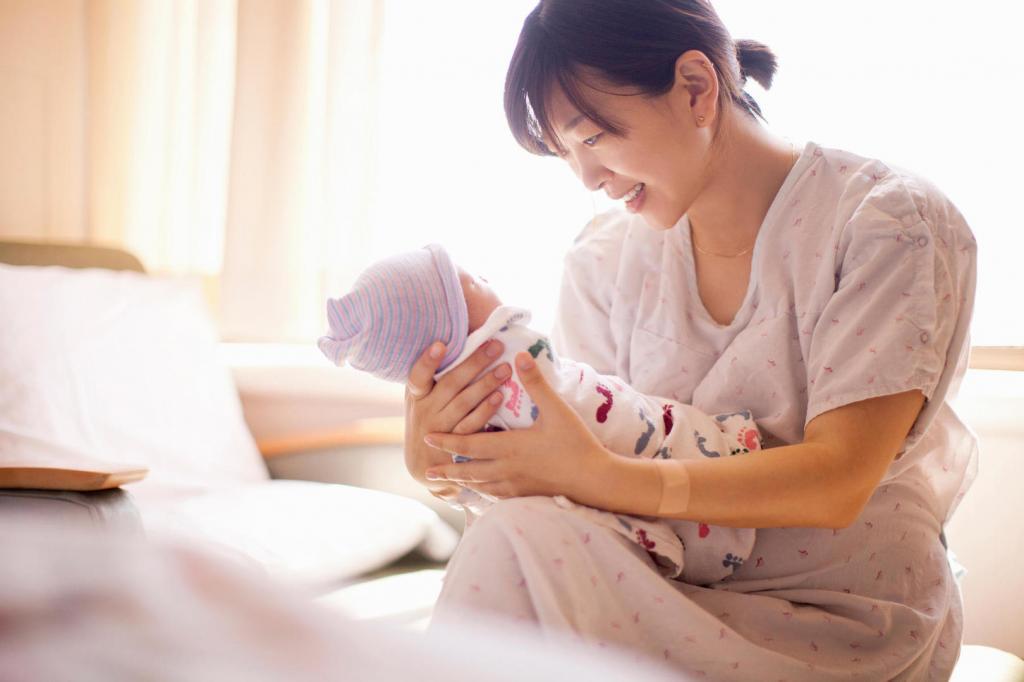 женщина держит на руках новорожденного ребенка