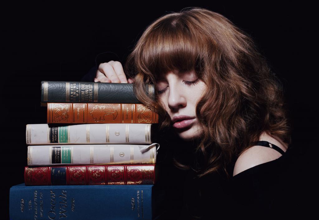 Девушка спящая на книгах