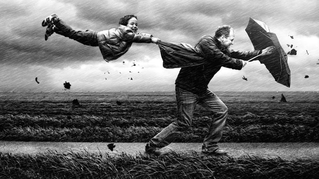 Люди идут против сильного ветра