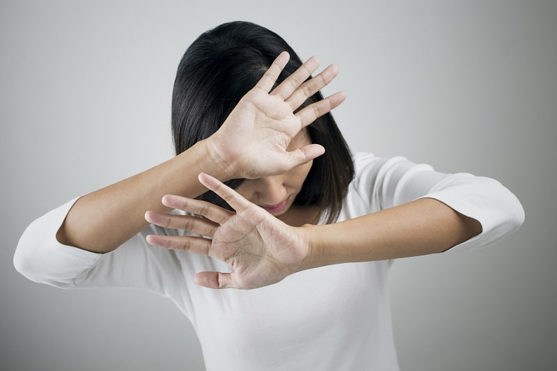Girl hiding behind her hands