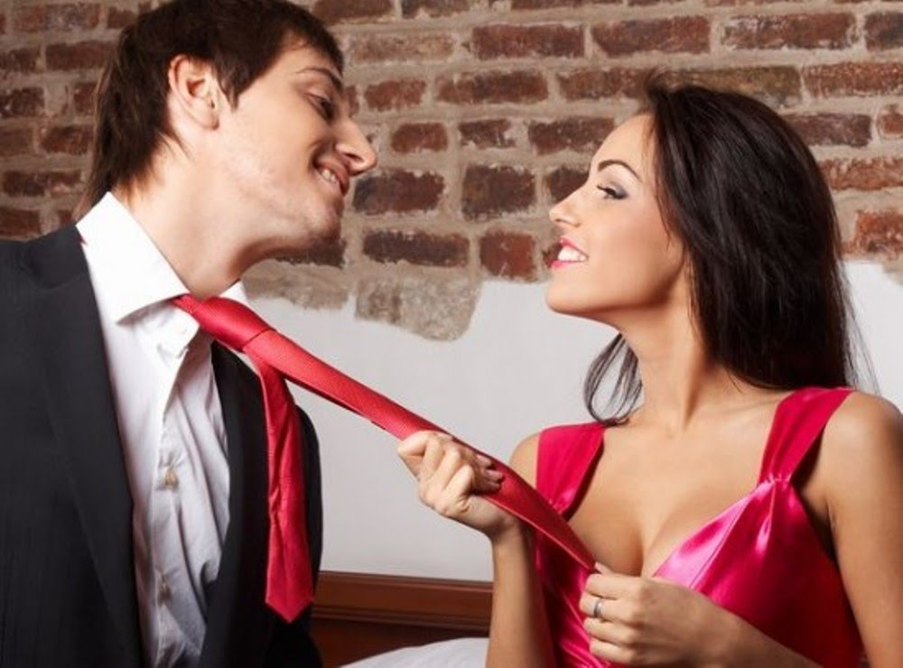 Girl holds a guy's tie