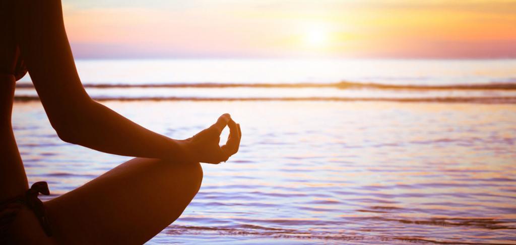 Девушка медитирует возле воды