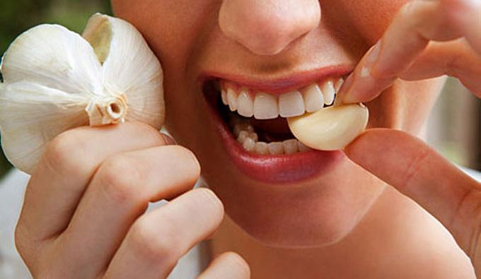 Девушка кусает чеснок