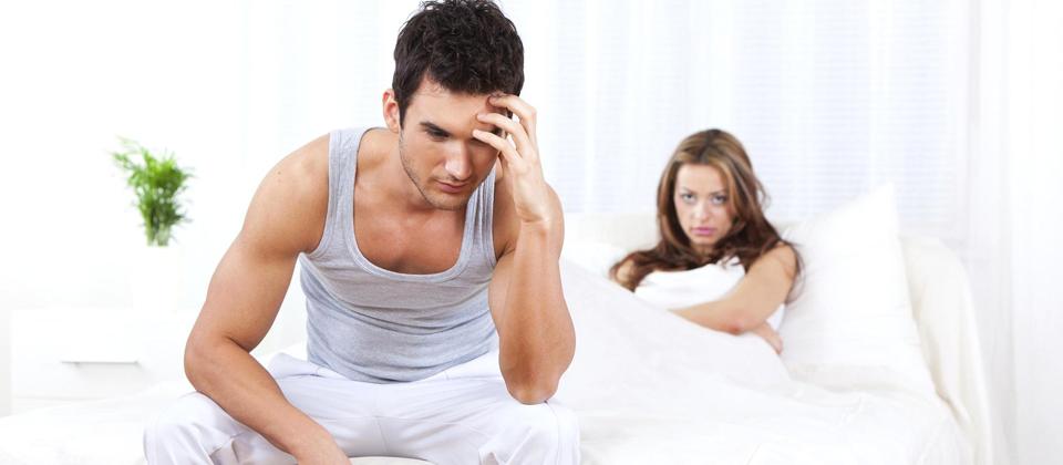 Мужчина сидит на кровати, сзади лежит девушка