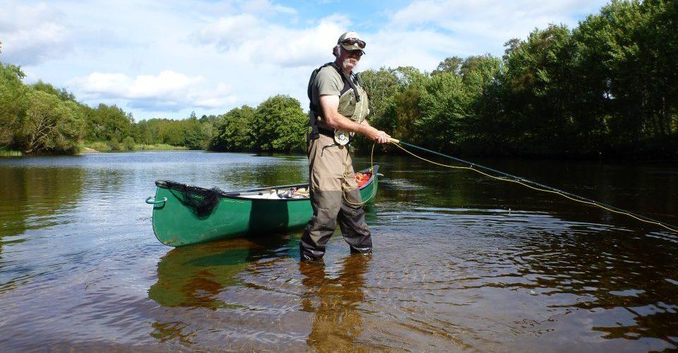 Мужчина рыбачит возле лодки.