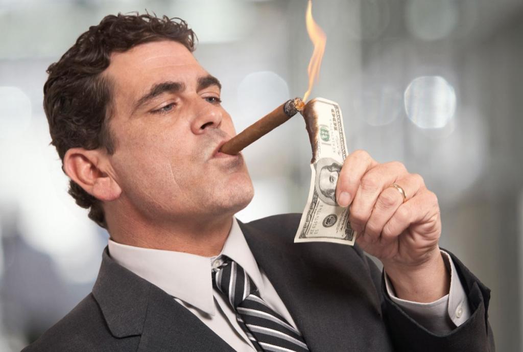 A rich man smokes a cigar.
