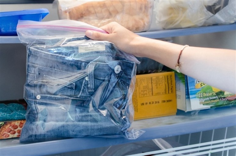 A girl takes out jeans from the refrigerator.