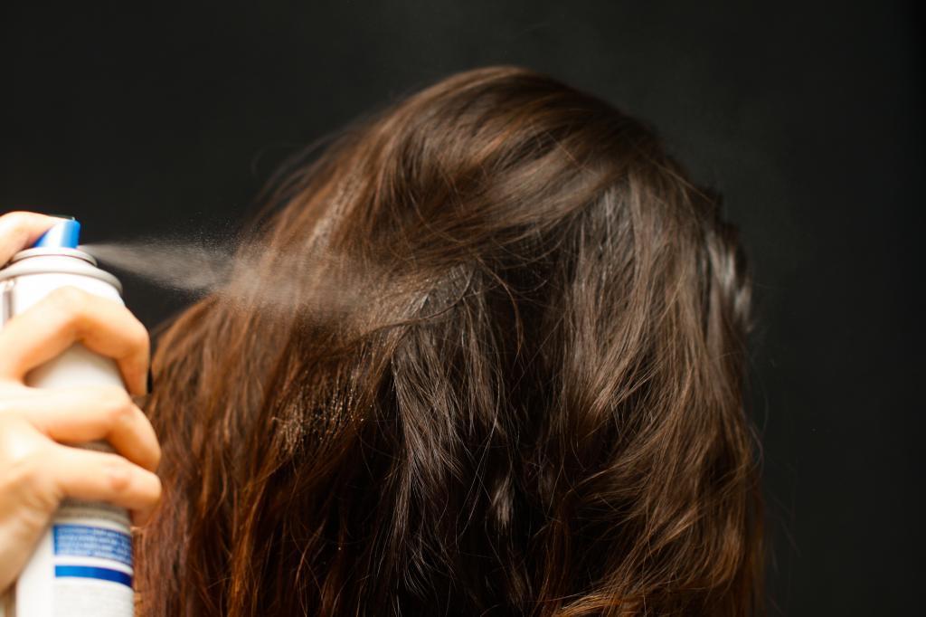 Girl uses hair spray.
