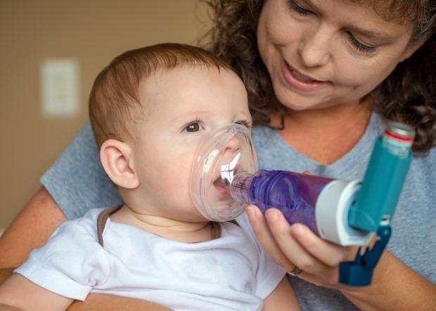 Mom helps an asthmatic child.